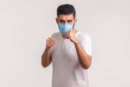 Man in surgical mask punching boxing to camera, fighting against contagious disease, coronavirus infection, respiratory illness such as flu, 2019-nCoV, ebola. studio shot isolated on white background