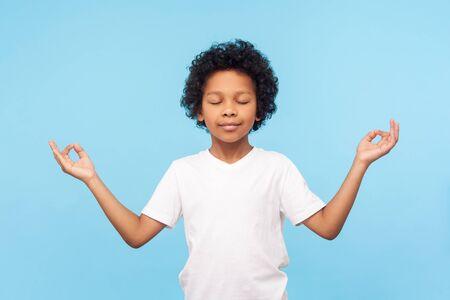 Retrato de niño pequeño lindo pacífico sosteniendo los dedos en gesto de mudra y meditando con los ojos cerrados, sintiéndose tranquilo, positivo y relajado, práctica de yoga. Foto de estudio de interior aislado sobre fondo azul.