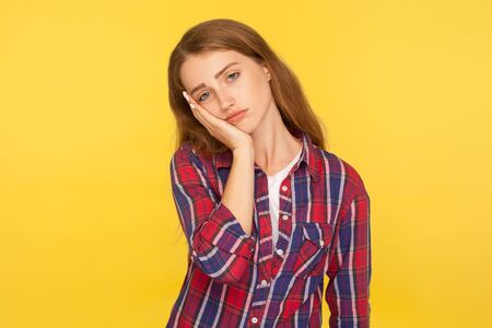 I'm bored! Portrait of depressed ginger girl in checkered shirt leaning on cheek and looking with indifferent dull expression, tired of boring story. indoor studio shot isolated on yellow background