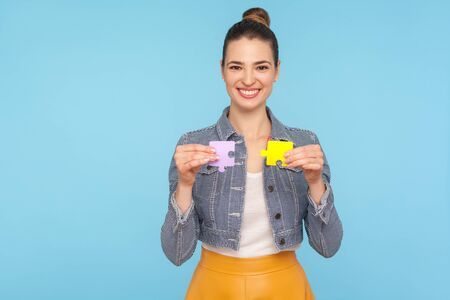 Fascinating joyful fashionably dressed woman with hair bun holding colorful pieces of puzzle, two parts of one, symbol of connection and union, association. studio shot isolated on blue background