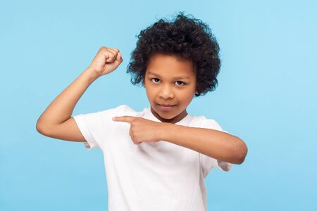 Look at my muscle, I'm strong. Portrait of adorable little boy in T-shirt pointing at biceps, feeling powerful and self-confident, showing strength. indoor studio shot isolated on blue background
