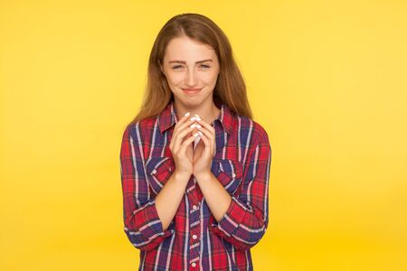 Portrait of cunning young ginger girl in checkered shirt smirking at camera, smiling slyly and thinking devious tricks in mind, scheming and conspiring evil idea, cheats. studio shot yellow background
