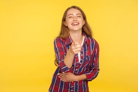 Hey you! Portrait of excited ginger girl in checkered shirt happily indicating at camera and laughing, pointing finger joking teasing, making fun of you. studio shot isolated on yellow background