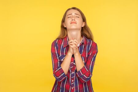 Please I'm begging! Portrait of despaired ginger girl in shirt keeping arms in prayer gesture and holding up head, appealing to god with imploring expression. studio shot isolated on yellow background