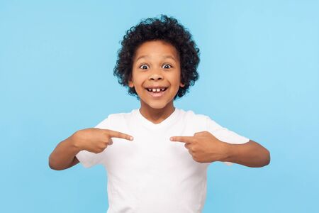 Wow, this is me! Portrait of amazed happy preschool boy in T-shirt looking at camera with shocked face and pointing himself, being proud and surprised. indoor studio shot isolated on blue background Stock fotó