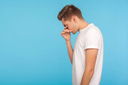 Side view of upset man in white t-shirt touching eyes, wiping away tears and crying quietly, feeling desperate and hopeless, lonely suffering depression. indoor studio shot isolated on blue background