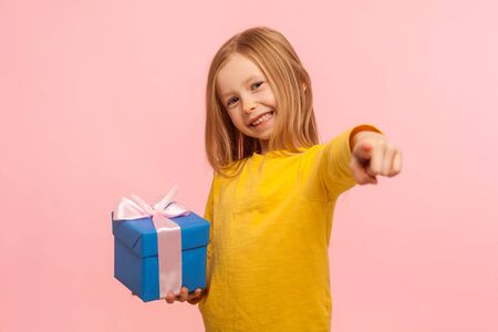 Portrait of kind generous little girl standing with gift box, bonus, pointing finger to camera and choosing lucky winner. indoor studio shot isolated on pink background