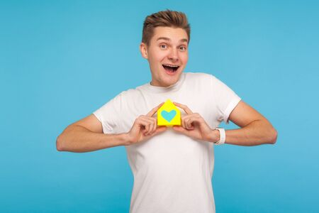 Enthusiastic happy man holding small paper home with heart inside and smiling to camera, satisfied with bought property, mortgage. studio shot isolated on blue background