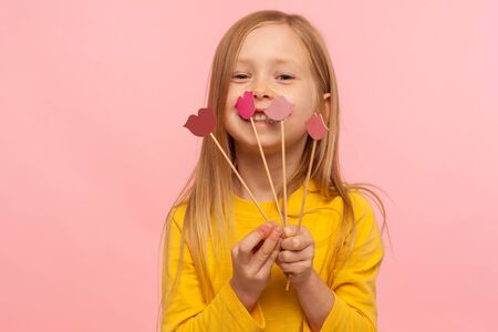 Portrait of lovely pretty little girl smiling, holding few red pink paper lips on sticks, choice of lipstick color, fashion and beauty care concept. indoor studio shot isolated on pink background
