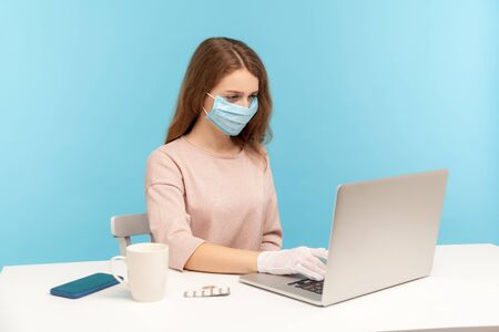 Office worker wearing facial mask and hygienic gloves while typing on laptop, protecting her hands and face to prevent contagious disease, viral infection, coronavirus 2019-ncov. indoor studio shot