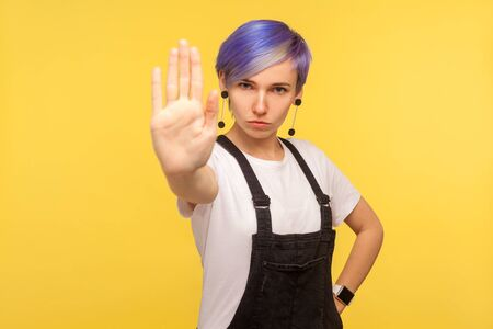 No, prohibited! Portrait of serious hipster woman with violet short hair in denim overalls showing stop gesture limit sign, saying enough, warning of danger. isolated on yellow background, studio shot