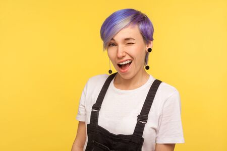 Portrait of excited cheerful hipster woman with violet dyed short hair in denim overalls winking at camera and smiling, flirting with friendly playful look. isolated on yellow background, studio shot