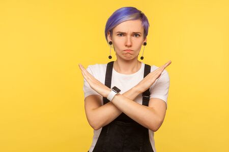 Portrait of serious hipster girl with violet short hair in denim overalls making x sign with crossed hands meaning definite no, never again, warning gesture. isolated on yellow background, studio shot