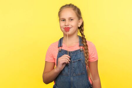Portrait of charming happy little girl with braid in denim overalls covering mouth with red paper lips on stick and smiling at camera, symbol of kiss. indoor studio shot isolated on yellow background
