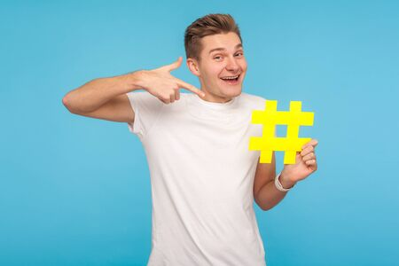 Check interesting blog. Cheerful funny man in t-shirt pointing at big yellow hashtag symbol and smiling, hash sign of internet trends, viral social media topic. indoor studio shot, blue background