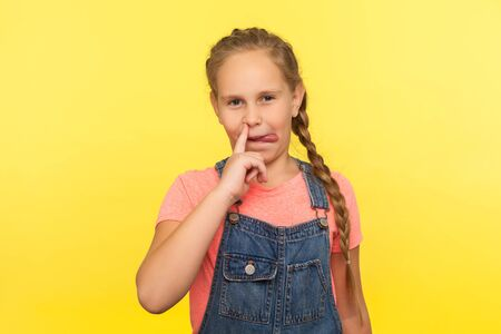 Bad manners. Portrait of funny cute little girl with braid in denim overalls picking nose and sticking out tongue, having fun, child behaving impolite. indoor studio shot isolated on yellow background Foto de archivo