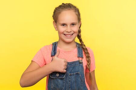 I like it! Portrait of charming pleased little girl with braid in denim overalls smiling at camera and gesturing thumbs up, approval hand sign, excellent feedback. indoor studio shot, isolated