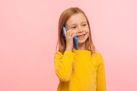 Cute little ginger girl with freckles smiling joyfully while calling parents on cell phone, good cellular, roaming, comfortable to use children mobile device. studio shot isolated on pink background
