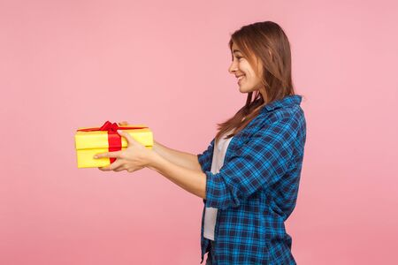 Take this present! Side view of generous girl in checkered shirt giving wrapped box and smiling kindly, sharing gift on christmas, charity concept. indoor studio shot isolated on pink background Stock Photo