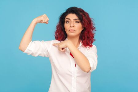 Look, I'm strong! Portrait of proud woman with fancy red hair pointing to biceps on raised hand, boasting female power to achieve success, feminism concept. studio shot isolated on blue background