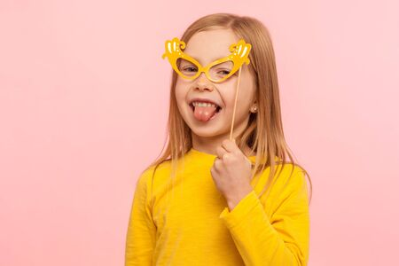 Portrait of charming ginger little girl covering eyes with paper glasses and sticking out tongue, naughty child having fun, wearing masquerade mask. indoor studio shot isolated on pink background