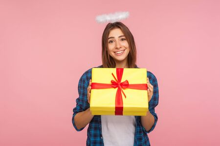 Present from angel. Portrait of generous happy beautiful girl with halo over head holding gift box and smiling kindly, congratulating on birthday. indoor studio shot isolated on pink background Stock Photo