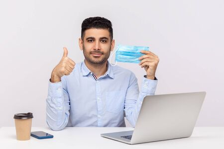 Businessman holding hygienic mask and showing thumb up, recommending to use excellent protect filter in office against contagious disease coronavirus, 2019-nCoV, flu epidemic. studio shot isolated