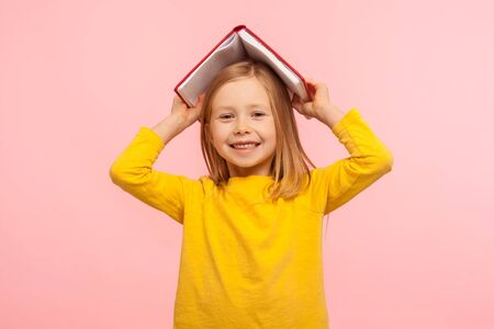 Portrait of happy lazy little girl covering head with book and smiling to camera, disobedient child having fun, fooling around instead studying lesson. indoor studio shot isolated on pink background