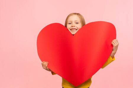 Portrait of sweet adorable little girl peeking out of large red heart symbol and smiling to camera, congratulating on Mothers day, saying I love you. indoor studio shot isolated on pink background Banco de Imagens