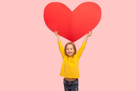 Portrait of sweet cheerful little girl raising large red heart symbol over head and smiling to camera, congratulating on Mothers day, saying I love you. indoor studio shot isolated on pink background