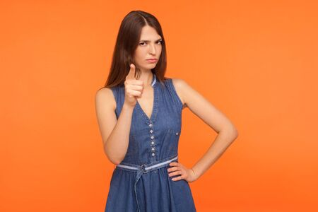 I told you! Strict angry brunette woman in denim dress scolding for mistake, dissatisfied with behavior, blaming showing admonishing gesture, warning sign. studio shot isolated on orange background