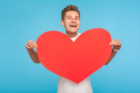 Happy Valentine day! Portrait of delighted cheerful man holding big red heart and smiling broadly to camera, declaration of love, romantic present. indoor studio shot isolated on blue background Banco de Imagens