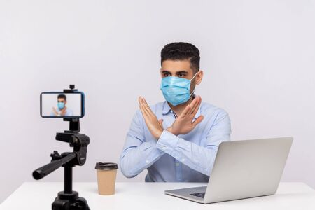 Man in medical mask gesturing stop with crossed hands, warning about coronavirus outbreak, dangerous contagious disease, making video about prevention of infection. studio shot, white background