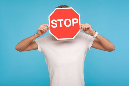 Portrait of unknown man in white t-shirt covering face with Stop symbol, anonymous person holding red traffic sign, warning to go, prohibition concept. indoor studio shot isolated on blue background