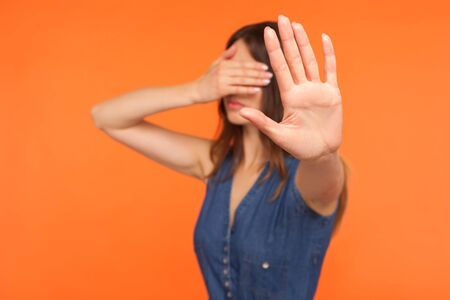 No, I won't look. Young brunette woman in denim dress covering eyes with hand showing stop gesture, rejecting to watch forbidden inappropriate content, ignoring problems. studio shot orange background