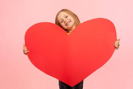 Portrait of sweet cheerful little girl peeking out of large red heart symbol and smiling to camera, congratulating on Mothers day, saying I love you. indoor studio shot isolated on pink background