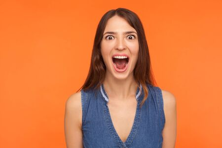 Excited impressed brunette woman in denim outfit standing with wide open mouth in surprise, looking startled at camera, expressing amazement shock. indoor studio shot isolated on orange background