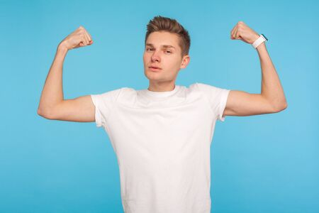 Im strong! Portrait of slim young man in casual white t-shirt raising hands to show biceps and looking confident at camera, feeling power and strength. indoor studio shot isolated on blue background Stok Fotoğraf