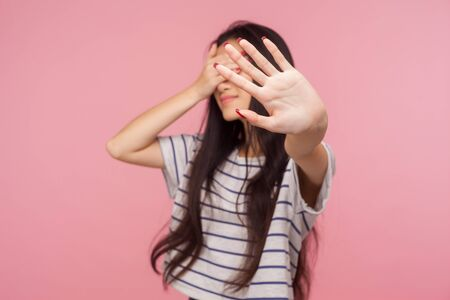 Portrait of displeased girl hiding eyes showing stop gesture, feeling disgusted by seen, refusing to look at shameful bad events, ignoring problem. indoor studio shot isolated