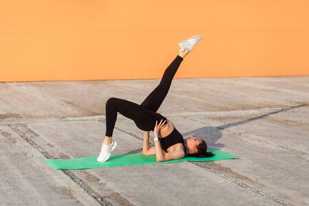Slim athletic girl in tight sportswear, black pants and top, practicing yoga, doing one legged bridge pose with leg raise, training muscles and flexibility. Health care, sport activity outdoor
