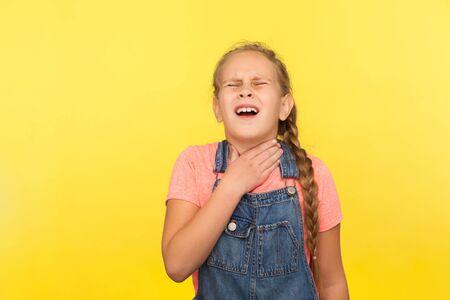 Flu symptoms, neck pain. Portrait of sick little girl in denim overalls suffering sore throat or tonsillitis, thyroid disorder, medical problem. indoor studio shot isolated on yellow background Imagens