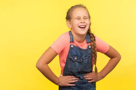 Portrait of unhealthy child with braid in denim overalls clutching belly, feeling discomfort or pain in stomach, young girl suffering constipation cramps. studio shot isolated on yellow background