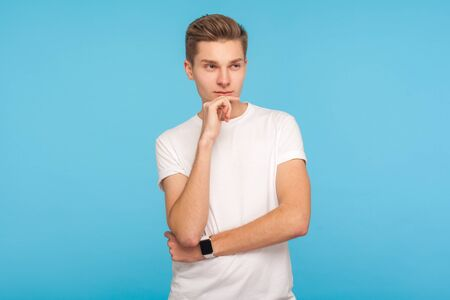 Portrait of serious pensive man in white t-shirt thinking over idea while holding chin with clever expression, having doubts about difficult question. indoor studio shot isolated on blue background