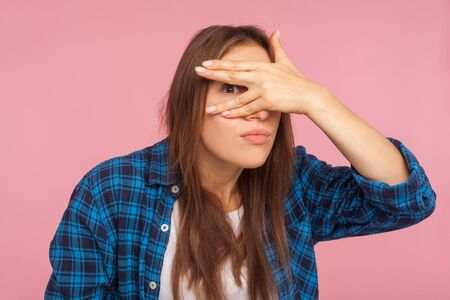 Portrait of nosy funny girl in checkered shirt peeking through fingers, looking with embarrassed inquisitive expression, watching secrets, spying rumors. indoor studio shot isolated on pink background Stock Photo