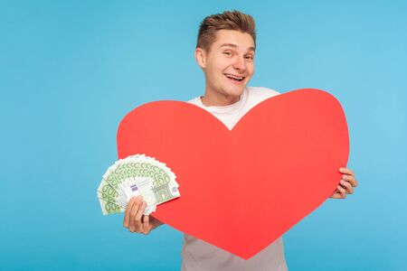 Happy cheerful rich young guy holding big red heart and euro banknotes, sincerely smiling at camera, buying gift, discounts and sales for Valentines Day. indoor studio shot isolated on blue background