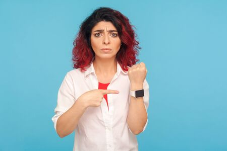 Displeased woman with fancy red hair showing wrist watch to remind of late hour, warning about deadline, looking impatient anxious. indoor studio shot isolated on blue background