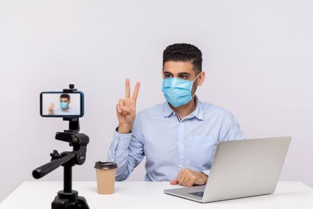 Man in hygienic mask gesturing victory making video about recovery after flu, coronavirus infection, giving tips on using protect filter against contagious disease. studio shot, white background Stock Photo