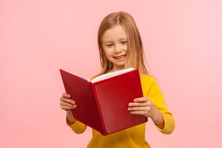 Smart positive cute little girl reading big red book and smiling happily, learning homework, being curious about school knowledge, education concept. indoor studio shot isolated on pink background