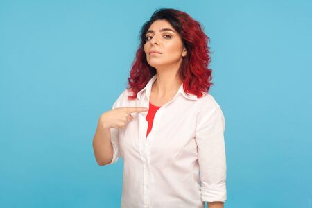 I'm the best! Portrait of egoistic hipster woman with fancy red hair pointing herself, looking with arrogance, feeling confident and self-important. indoor studio shot isolated on blue background Banco de Imagens