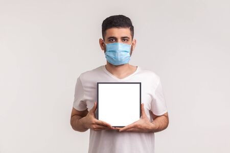 Man in hygienic mask holding white poster, mockup template, advertising area for warning information about coronavirus epidemic, Covid-19 quarantine, infectious disease, flu prevention. studio shot